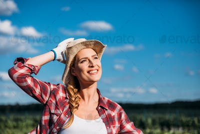 beautiful smiling young female farmer looking away while working on field