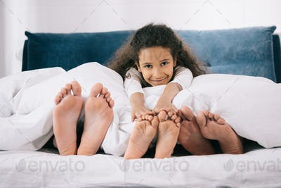 Adorable smiling girl lying in bed with father and mother