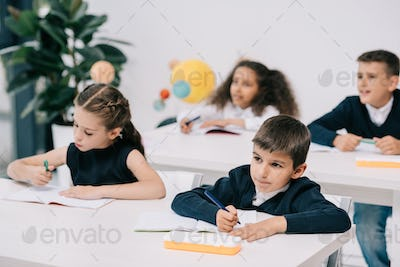 Cute little schoolchildren sitting at desks and writing in exercise books