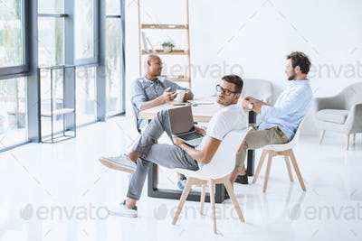 multicultural group of businessmen sitting at workplace in light modern office