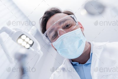 Camera Point of View of dentist in white coat, protective mask and glasses in dental clinic