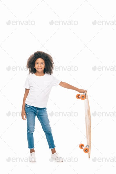 cute african american girl holding skateboard and smiling at camera isolated on white