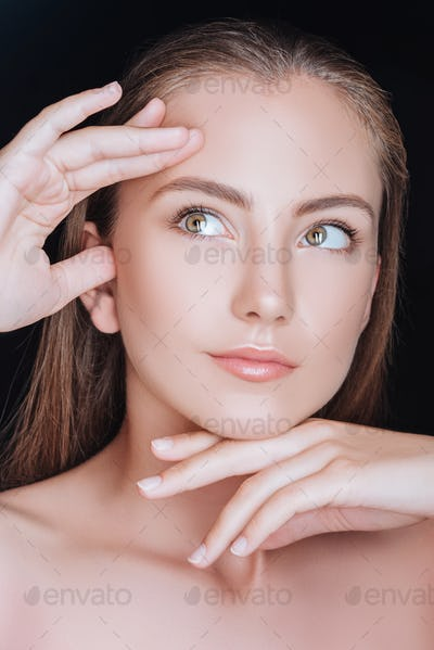 portrait of beautiful dreamy woman with hands near face isolated on black