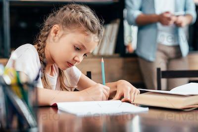 cute focused little girl writing homework