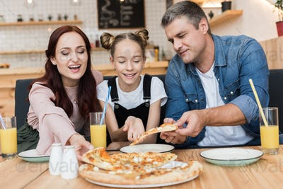 happy family with teen daughter eating pizza in cafe