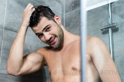 handsome happy young man taking shower