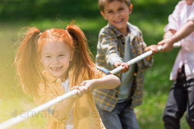 adorable happy little kids playing tug of war in park