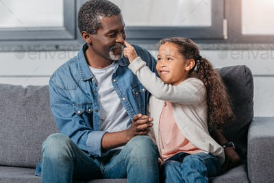 Adorable african american girl touching fathers nose at home