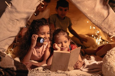 smiling girls with lighter reading book in handmade tent at home