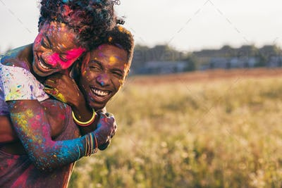 portrait of happy african american couple piggybacking at holi festival