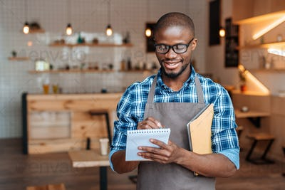 handsome smiling african american waiter taking order with notepad and digital tablet in coffee shop