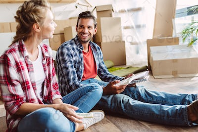 smiling young couple counting money while sitting on floor in new apartment