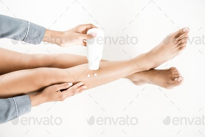 cropped shot of woman applying body cream on legs isolated on white