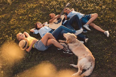 smiling multiethnic teenagers with dog playing guitar while lying together on grass