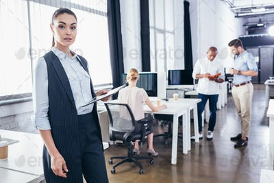 young businesswoman with digital tablet looking at camera while colleagues working behind