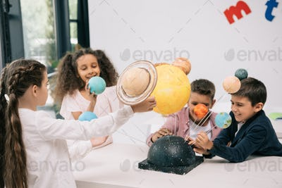 Multiethnic group of schoolchildren working with solar system model in classroom