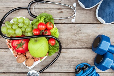 top view of stethoscope, organic vegetables and fruits and sport equipment on wooden surface,
