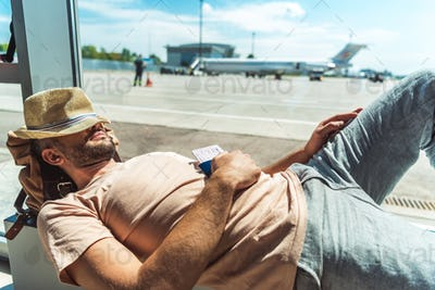 traveler with passport and ticket in hand sleeping in airport