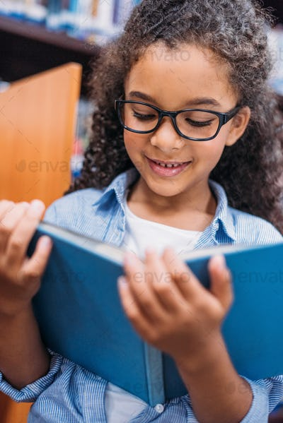close-up portrait of african american schoolgirl reading book