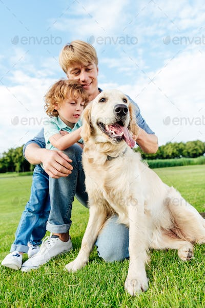happy father and son stroking golden retriever dog at park