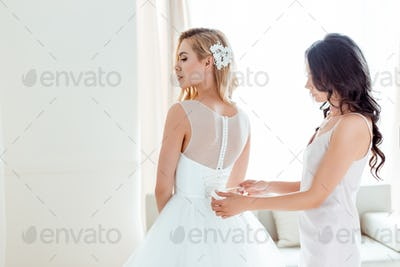 beautiful young bridesmaid dressing up bride for wedding