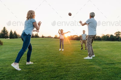 happy grandparents playing american football with grandchildren in park