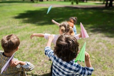 cute little children throwing paper planes in park