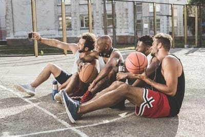 multiethnic group of men taking selfie on smartphone while sitting on court after basketball game