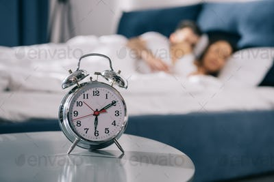 Close-up view of alarm clock standing on table in bedroom at morning