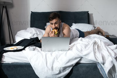 bearded young man using laptop and eating sandwich while lying in bed at morning