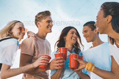 smiling friends clinking plastic glasses with alcohol outdoors
