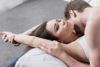 attractive passionate couple making love in bed at morning