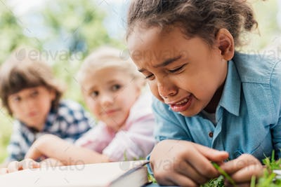 close-up view of little african american girl crying while friends lying on grass behind