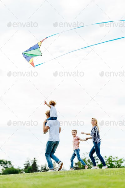 happy family with two kids playing with kite at park