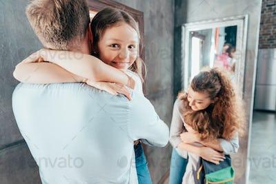 adorable parents hug kids before school
