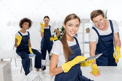 smiling young female cleaner using digital tablet while colleagues working behind