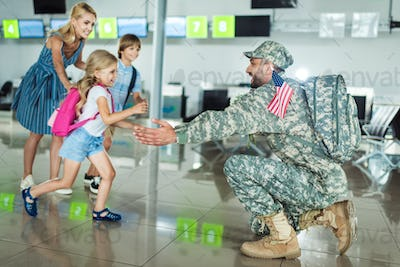happy family meeting father in military uniform at airport