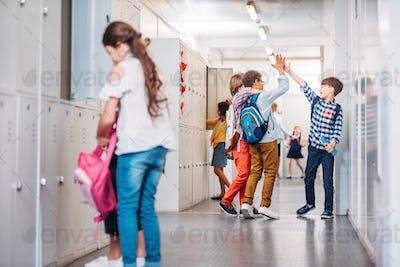 boys giving high five in school corridor while girl putting books into locker