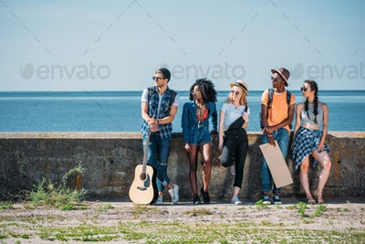 multicultural group of young people with empty cardboard standing a parapet while hitchhiking