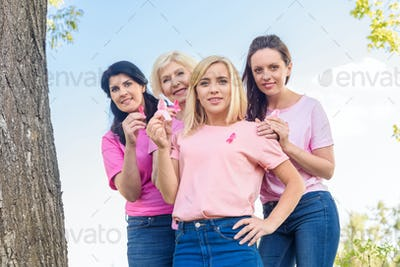 women in pink t-shirts holding breast cancer awareness ribbons and smiling at camera