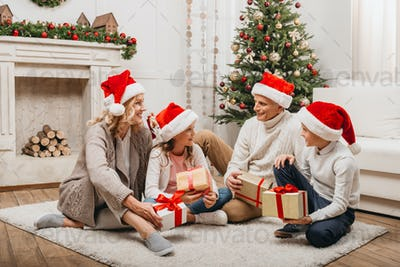 smiling grandparents and kids with gift boxes in christmas decorated room
