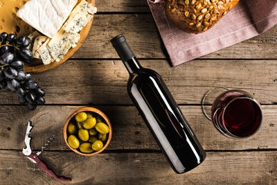 top view of bottle of red wine, corkscrew, wineglass, green olives, different cheese and bread on