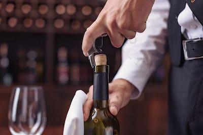 Cropped image waiter opening wine bottle with corkscrew