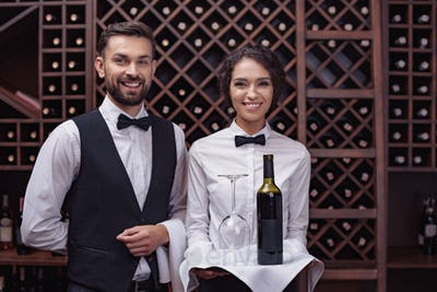 Portrait of young waiters standing with bottle of red wine and glass on tray in cellar