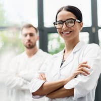 Beautiful young scientist in eyeglasses smiling at camera while colleague standing behind