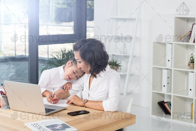 asian businesswoman working while daughter hugging her in modern office