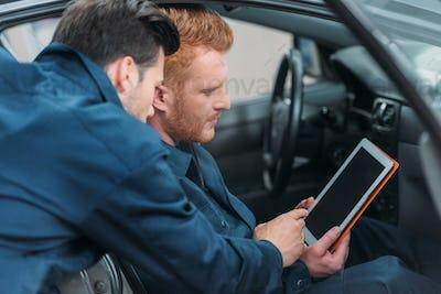 Two car mechanics sitting in a car at workshop using a digital tablet.