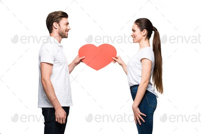 young smiling couple holding red heart, isolated on white