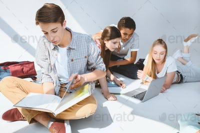 teenage boy reading book while multicultural friends using laptop on white