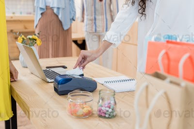 cropped shot of woman paying with credit card in store